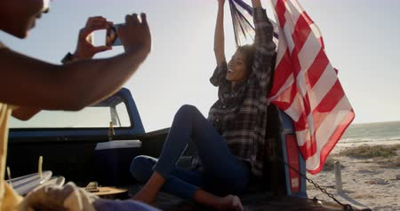 ピックアップ : African american man taking photos of woman with mobile phone on the beach. She is holding American flag 4k