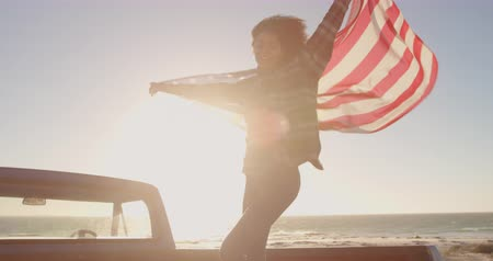 baixo ângulo : Low angle view of African american woman standing with waving american flag on a truck. She is dancing 4k