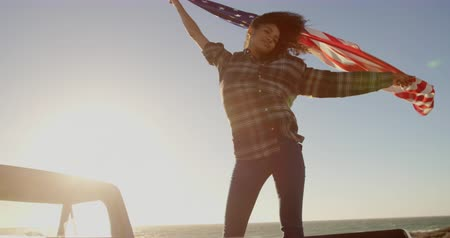 etnia africano : Low angle view of African american woman waving american flag on pickup truck at beach. She is closed her eyes 4k Stock Footage