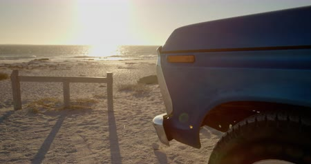 yokluk : Blue pickup truck parked on the beach. Beautiful sea in the background 4k Stok Video