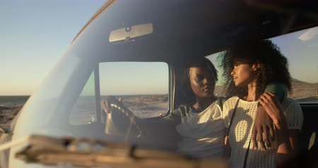 fele olyan hosszú : Front view of African american couple sitting together in pickup truck a beach. They are looking each other 4k