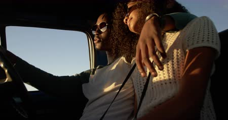 отдыха : Low angle view of African american couple sitting together in pickup truck a beach. They are wearing sunglasses 4k Стоковые видеозаписи