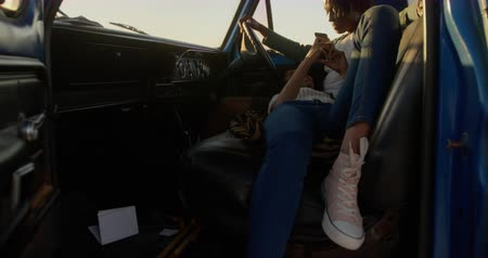 mansão : Front view of African american woman lying on mans lap in a pickup truck at beach. She is using mobile phone 4k