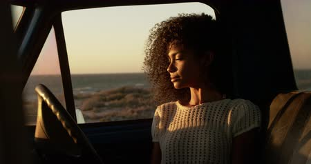 ona : Front view of African american woman sitting in pickup truck at beach. She is looking away 4k