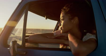 etnia africano : Front view of African american woman leaning on window of pickup truck at beach. She is looking away 4k