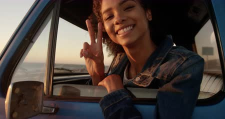 ピックアップ : Front view of African american woman showing victory sign in pickup truck at beach. She is smiling and looking at camera 4k