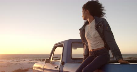 ピックアップ : Front view of African american woman sitting on trunk of pickup truck at beach. She is looking away 4k