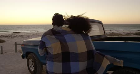 ピックアップ : Rear view of African american couple wrapped in blanket and walking together near pickup truck. They are smiling and having fun. Beautiful sunset in background 4k 動画素材