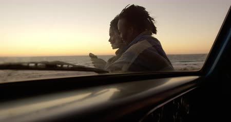 ピックアップ : Side view of African american couple wrapped in blanket near pickup truck at beach during sunset. They are interacting with each other 4k 動画素材