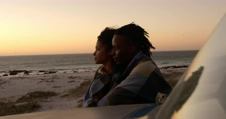 плечи : Side view of African american couple wrapped in blanket near pickup truck at beach during sunset. They are looking away 4k