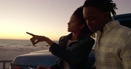 yol tarifi : Front view of African american woman pointing finger and showing something to man on beach. They are holding map 4k Stok Video