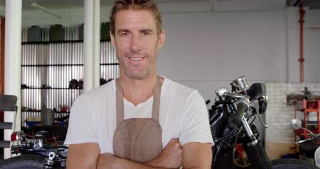 authenticity : Front view of Caucasian male mechanic standing with arms crossed in motorbike repair garage. He is smiling and looking at camera 4k Stock Footage