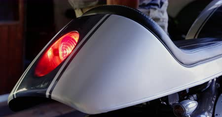 brake : Close-up of mechanic checking motorbike brake light in repair garage. Red brake light blinking 4k