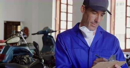 authenticity : Front view of Caucasian male mechanic writing on clipboard in motorbike repair garage. He is looking at camera 4k