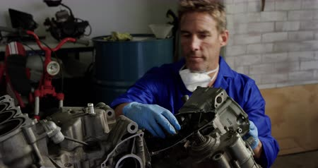 authenticity : Front view of Caucasian male mechanic repairing motorbike parts in repair garage. He is fixing motorbike engine 4k Stock Footage
