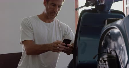 authenticity : Front view of Caucasian male mechanic using mobile phone in motorbike repair garage. He is smiling and texting text 4k Stock Footage