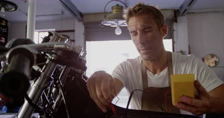 authenticity : Front view of Caucasian male mechanic checking battery of motorbike in repair garage. He is using multimeter 4k Stock Footage