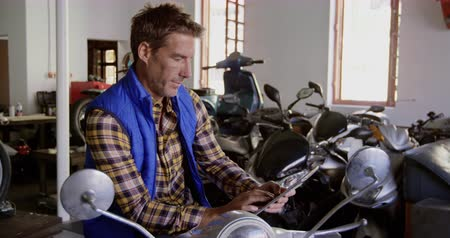 spare : Side view of Caucasian male mechanic using digital tablet in motorbike repair garage. He is sitting on scooter 4k Stock Footage