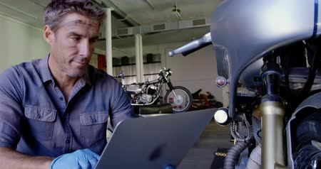 authenticity : Front view of Caucasian male mechanic using laptop in motorbike repair garage. He is looking at motorbike 4k