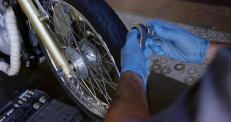 スパナ : Mid section of Caucasian male mechanic repairing motorbike in repair garage. He is using spanner 4k