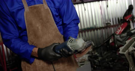earmuffs : Front view of Caucasian male mechanic working in repair garage. He is using angle grinder 4k