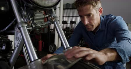 servicing : Front view of Caucasian male mechanic repairing motorbike in repair garage. He is fixing motorcycle front fender 4k Stock Footage