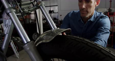authenticity : Front view of Caucasian male mechanic repairing motorbike in repair garage. He is fixing motorcycle front fender 4k Stock Footage