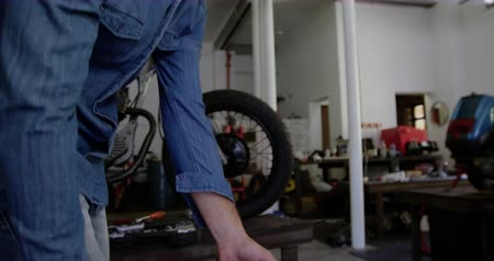 servicing : Side view of Caucasian male mechanic pushing motorcycle wheel in repair garage 4k Stock Footage