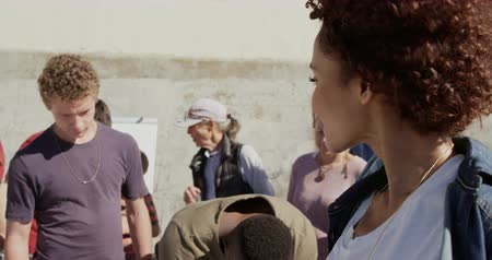 voluntary : Front view of African american female volunteer looking at camera on the beach. Volunteers filling form 4k Stock Footage