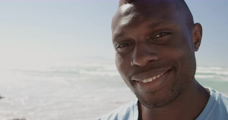 voluntary : Front view of African american male volunteer looking at camera on the beach. He is smiling 4k