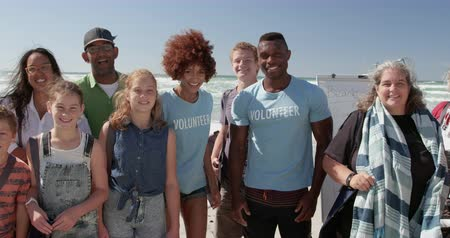 voluntary : Portrait of diverse volunteers standing together on beach in the sunshine. They are smiling and looking at camera 4k