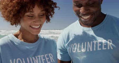 voluntary : Portrait of front view of African american volunteers looking at clipboard on the beach. They are smiling 4k Stock Footage
