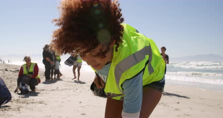 ajoelhado : Front view of African american female volunteer cleaning beach on a sunny day. She is picking up trash 4k Stock Footage