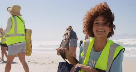 voluntary : Front view of African american female volunteer cleaning beach on a sunny day. She is smiling and looking at camera 4k