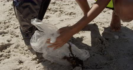 wolontariusz : Low section of female volunteer cleaning beach on a sunny day. She is picking up trash 4k