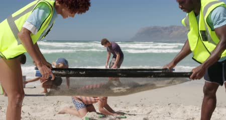 thrash : Side view of diverse volunteers cleaning beach on a sunny day. They are participating in beach cleanup 4k Stock Footage