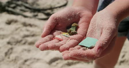 voluntary : Mid section of Caucasian volunteer girl holding waste in her hands on the beach. She is participating in beach cleanup 4k Stock Footage