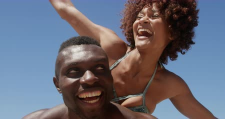 provést : Low angle view of young African american shirtless man giving piggyback ride to woman at beach. They are smiling and having fun 4k