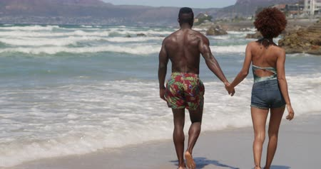 teljes hosszúságú : Rear view of young African american couple walking together on beach in the sunshine. They are holding hands 4k Stock mozgókép