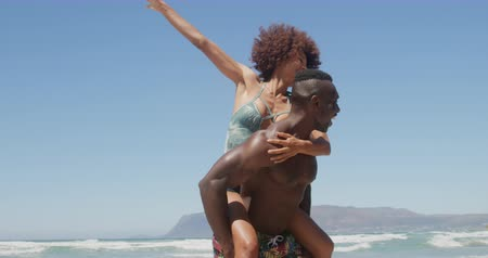 растягивается : Front view of young African american shirtless man giving piggyback ride to woman at beach. They are smiling and having fun 4k Стоковые видеозаписи