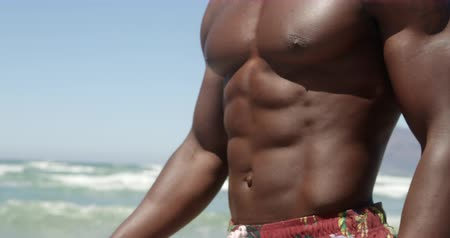 o : Mid section of muscular African american man walking on beach in the sunshine. He is shirtless 4k