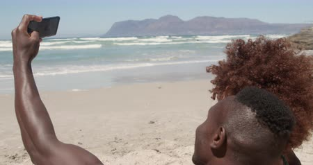 gömleksiz : Side view of young African american couple taking selfie with mobile phone on the beach. They are having fun 4k Stok Video