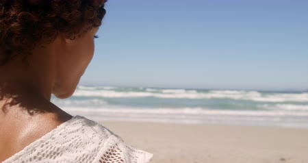 etnia africano : Rear view of young African american woman relaxing on beach in the sunshine. She is looking away 4k Stock Footage