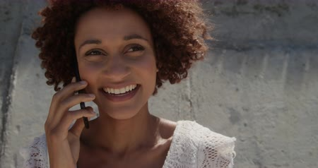 女性たち : Front view of young African american woman talking on mobile phone at beach in the sunshine. She is smiling and looking away 4k