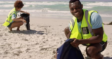voluntary : Front view of African american male volunteer cleaning beach on a sunny day. He is smiling and looking at camera with African american female volunteer in the background 4k Stock Footage