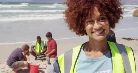 voluntary : Front view of African american female volunteer looking at camera on the beach. She is smiling with diverse volunteers in background. 4k
