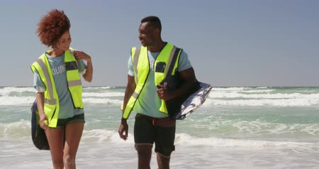 teljes hosszúságú : Front view of African american volunteers with garbage bag walking together on the beach. They are interacting with each other 4k Stock mozgókép
