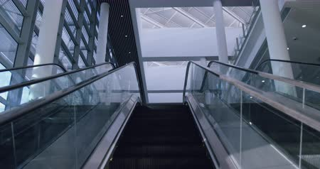 conveniente : Low angle view of Modern escalator in a office lobby. Escalator moving upwards 4k