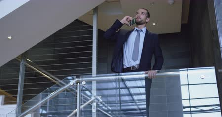 merdiven : Front view of Caucasian Businessman talking on mobile phone near staircase in office. He is standing near railing 4k Stok Video