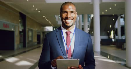 konference : Front view of African american Businessman looking at camera in a modern office. He is smiling 4k